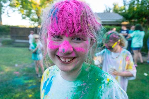 Girl covered in pink, green, blue and yellow powder.